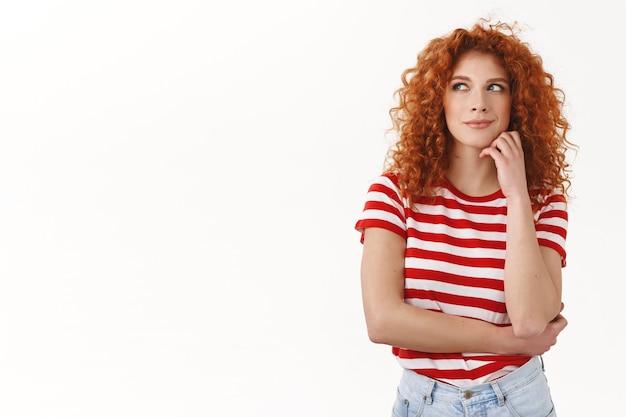 Коварная, умная, красивая, креативная, привлекательная рыжая, кудрявая европейка, имеет отличный план, ухмыляется, интриги, взгляд в сторону задумчивый, думающий, образующий идею, белая стена