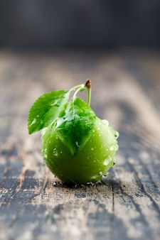 Dewy green plum with leaves side view on wooden and grungy wall