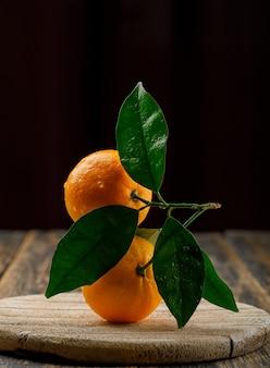 Росные апельсины на деревянной доске с боковым видом на черный и деревянный стол