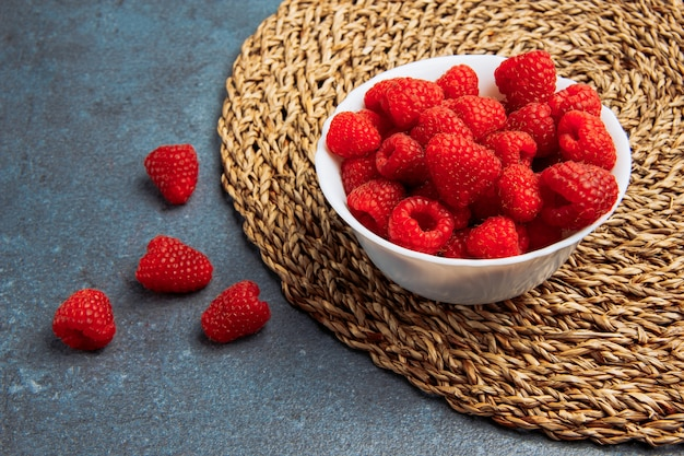 Dewy raspberries in a white bowl high angle view on a abstract grunge and wicker placemat background