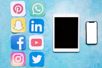 Dgital tablet and mobile phone near stickers of social media icons
