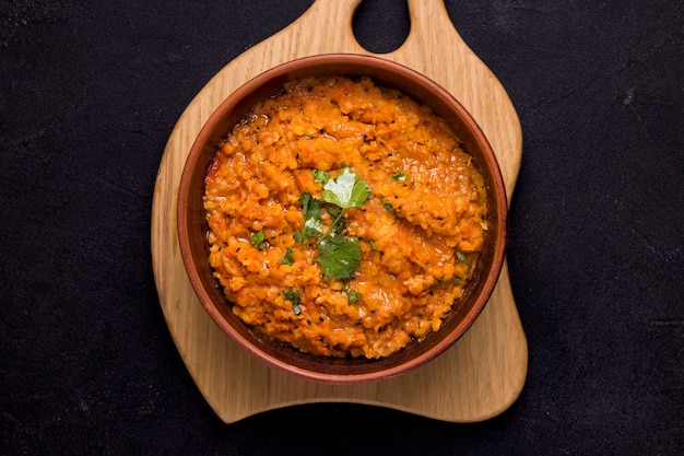 Dhal indian cream bean soup in a bowl on a wooden plank on black