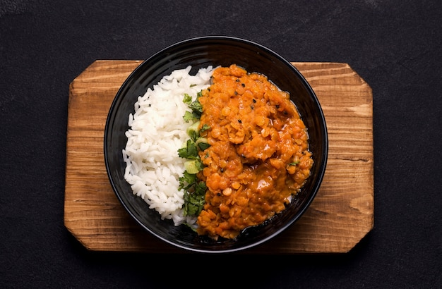 Dhal indian cream lentil soup on a wooden plank on black
