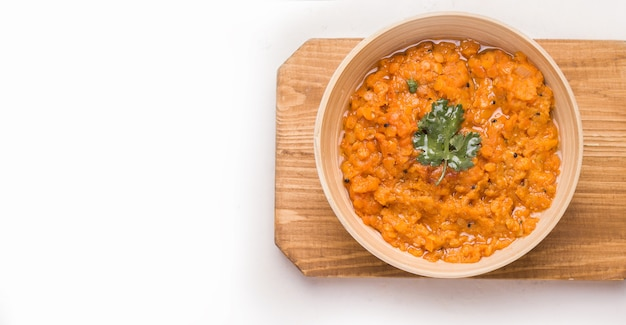 Dhal indian lentil soup with cilantro in a bowl on a wooden plank