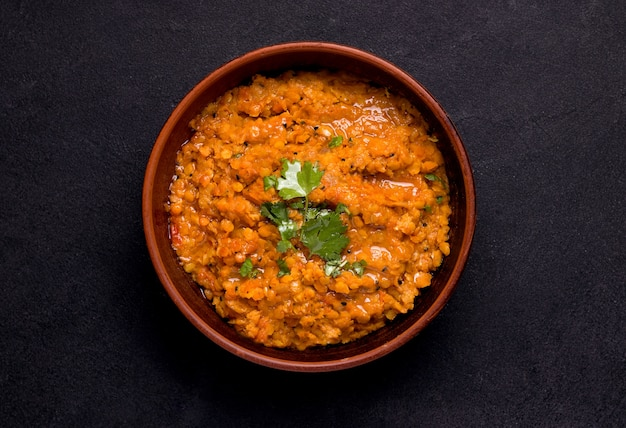 Dhal indian soup of red lentils and spices on black Premium Photo