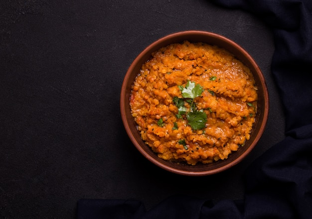 Dhal indian traditional lentil soup in a clay bowl on black