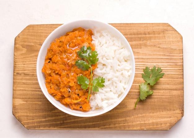 Индийское вегетарианское блюдо дхал в тарелке на деревянной доске