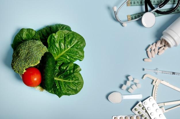 당뇨병 인식의 날 개념, 11월 14일. 흩어져 있는 약, 정제의 물집, 인슐린 주사기, 청진기, 측정 테이프, 파란색 배경에 정제된 설탕, 건강한 채식주의 음식.