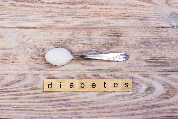 Diabetes block wooden letters and sugar pile on a spoon