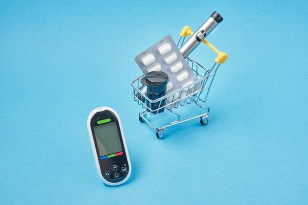 糖尿病の概念。青の背景にショップトロリーの糖尿病用品。