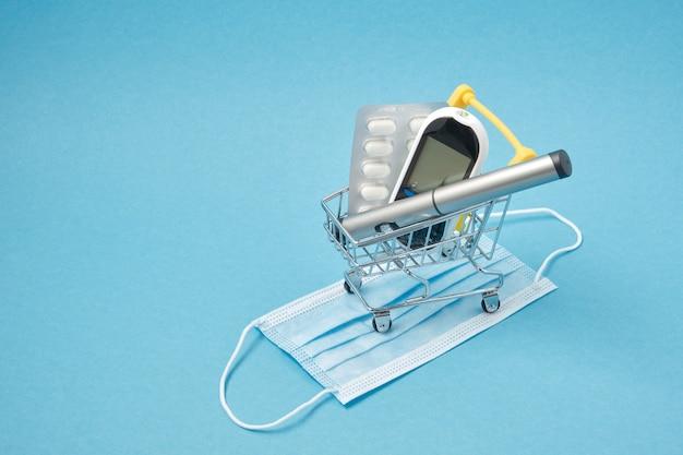Концепция диабета. диабетические принадлежности в магазинной тележке, таблетки, глюкометр, инсулиновая шприц-ручка на синем фоне