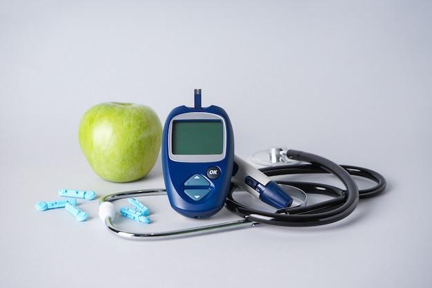 Концепция диабета с цифровым глюкометром, ланцетной ручкой, стетоскопом и яблоком