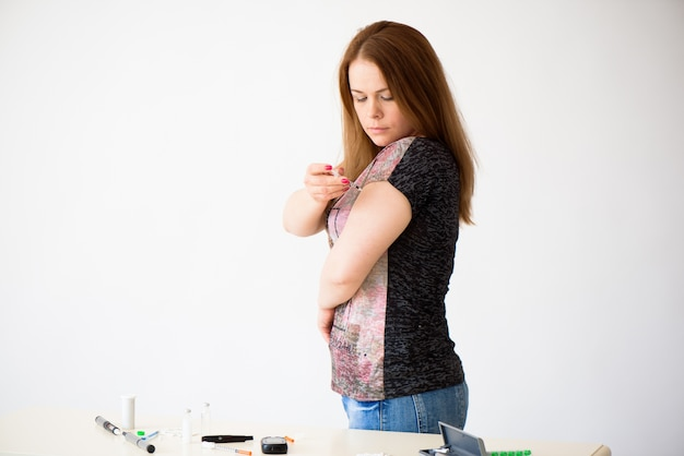 糖尿病に依存する女性が、注射器でヒューマログを注射してヒトインスリンワクチン接種を行っており、白い背景に皮下腕注射療法を行っています。