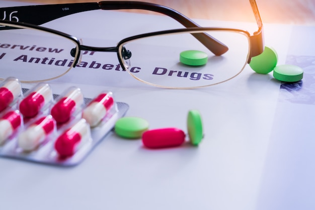 Diabetes drugs and glasses placed on textbook. diabetes mellitus type 2 concept.