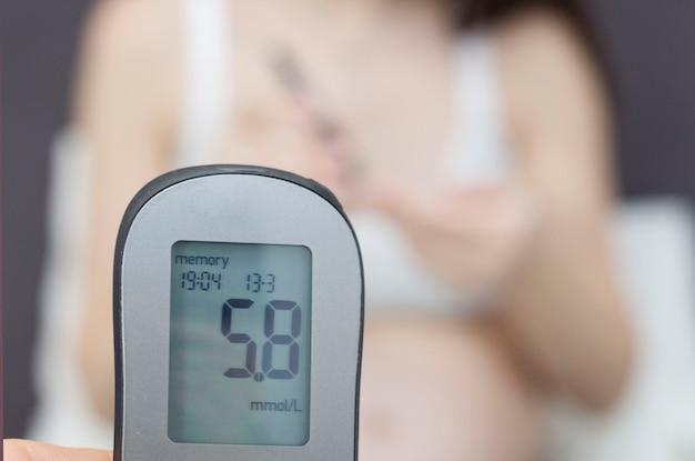 Сахарный диабет беременных. беременная женщина с желудком измеряет уровень глюкозы в крови глюкометром.