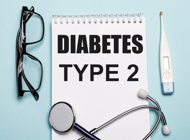 Диабет типа 2 написано на белом блокноте рядом со стетоскопом, очками и электронным термометром на голубой поверхности. медицинская концепция.