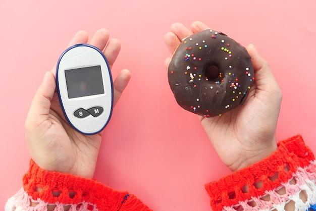 Инструменты измерения диабета и пончики на руке женщин