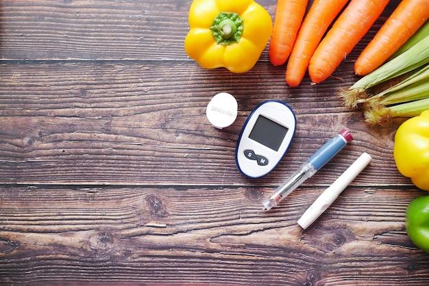 テーブルの上の糖尿病測定ツールと新鮮な野菜