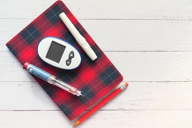 テーブルの上の糖尿病測定ツールとインスリンペン