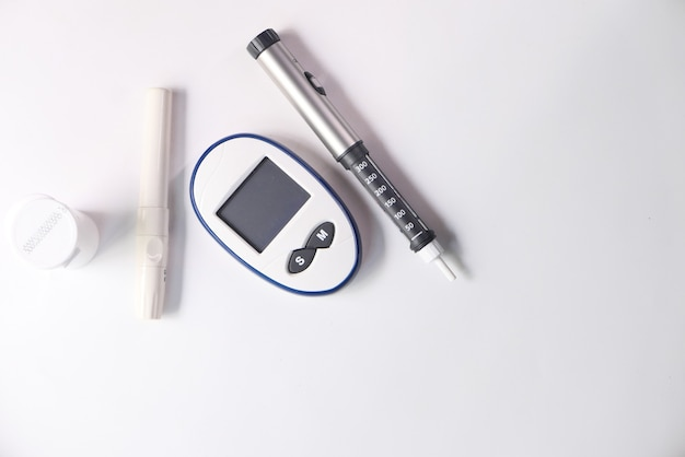 Diabetic measurement tools and insulin pen on table .