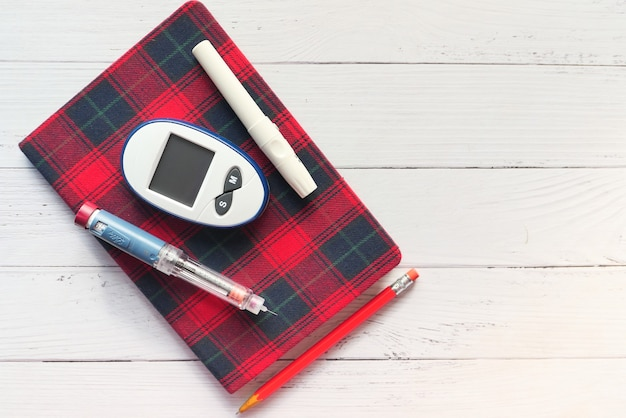 Diabetic measurement tools and insulin pen on table