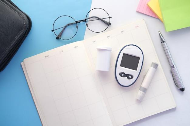 Инструменты измерения диабета на ежедневнике на столе