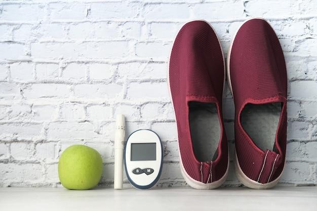 テーブルの上の糖尿病測定ツール、靴とリンゴ