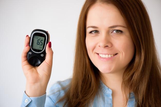 糖尿病患者は血中のブドウ糖のレベルを測定します。糖尿病の概念。白い背景の上の糖尿病用品。
