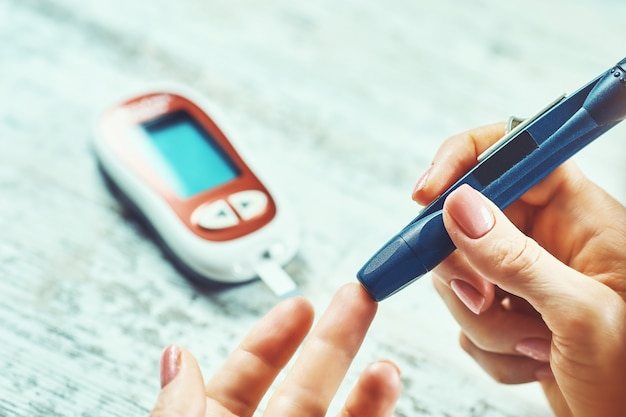 Женщина с диабетом, использующая глюкометр, женские руки держат глюкометр с ланцетной ручкой на пальце, измеряют уровень сахара и проверяют инсулин