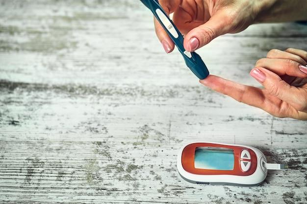 Женщина с диабетом, использующая глюкометр, женские руки держат глюкометр с ланцетной ручкой на пальце, измеряют уровень сахара, проверяют инсулин