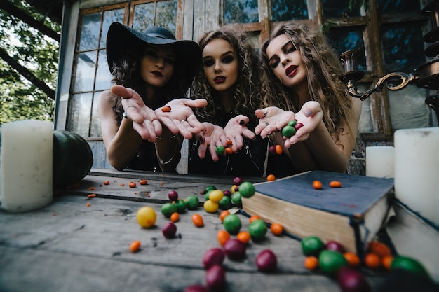 Diabolical witches throwing candies