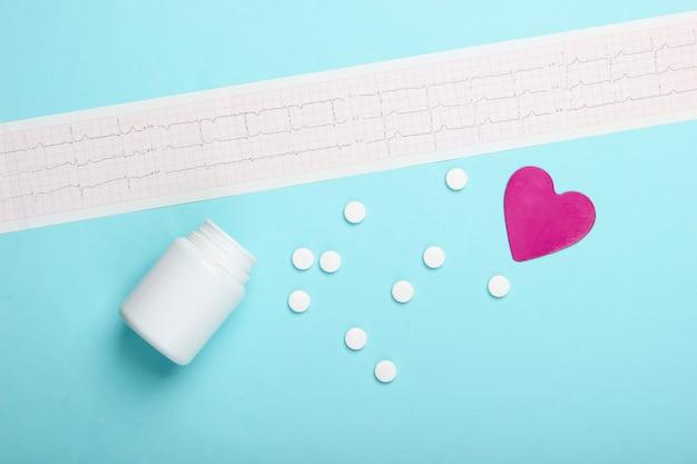 Диагностика и профилактика (лечение) сердечно-сосудистых заболеваний. кардиограмма сердца, бутылка таблетки, декоративное сердце на синем фоне. здоровое сердце. вид сверху