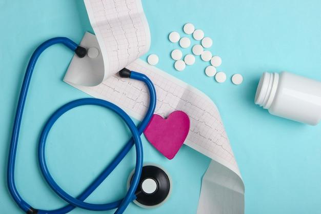 Диагностика и профилактика (лечение) сердечно-сосудистых заболеваний. кардиограмма сердца, стетоскоп, бутылка таблеток на синем фоне. здоровое сердце. вид сверху