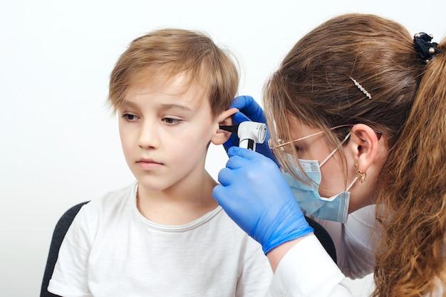 어린이의 장애 진단 및 청력 검사. 이경을 사용하여 소년의 귀를 검사하는 의사. 이경으로 작은 환자를 검사하는 소아과 의사. 아동청력검사.