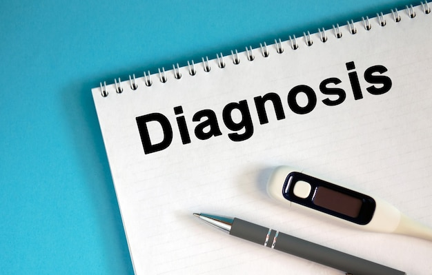 Diagnosis - text on a notepad. lie a pen and a medical thermometer