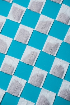 Diagonal closed white tea bags pattern on blue background