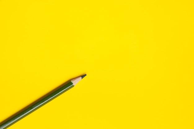 明るい黄色の背景に斜めの濃い緑色の鋭い木製の鉛筆、孤立した、コピースペース、モックアップ