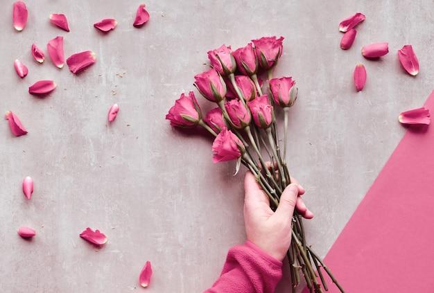 石の斜めの幾何学的な紙の背景。フラット横たわっていた、ピンクのバラを保持している女性の手、散らばった花びら、バレンタインの日。