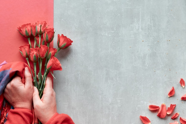 Diagonal geometric paper wall on stone. flat lay, female hands hold red roses and vibrant trendy color scarf, scattered petals. top view, concept for valentine's day, birthday or mother's day.