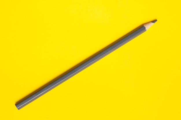 Diagonal gray sharp wooden pencil on a bright yellow background, isolated, copy space, mock up