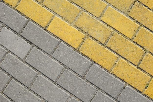 대각선 회색 및 노란색 포장 석판 평면도. 거리 도로로 벽돌, 포장 돌 질감. 추상 이중 색상 포장 돌 배경입니다.