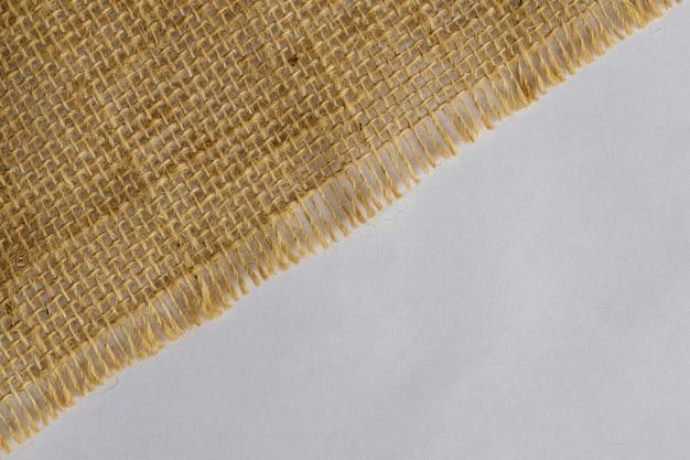 Diagonal jute fabric texture on white background.