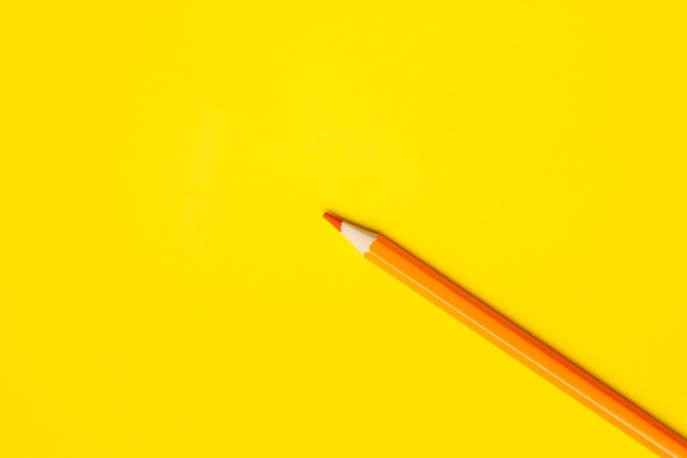 Diagonal orange sharp wooden pencil on a bright yellow background, isolated, copy space, mock up