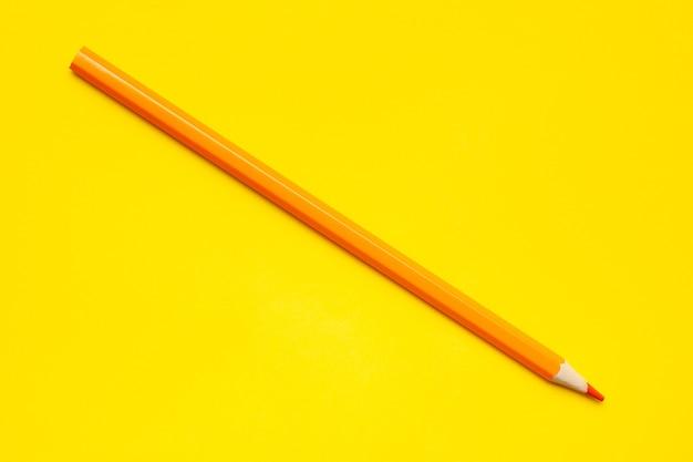 明るい黄色の背景に斜めのオレンジ色の鋭い木製の鉛筆、孤立した、コピースペース、モックアップ