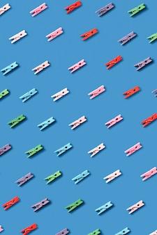Диагональный узор из рисунка для стирки из разноцветных прищепок на синей стене.