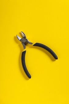 Диагональные плоскогубцы на желтом фоне используются для резки проводов в электричестве. необходимый инструмент для мастера-электрика