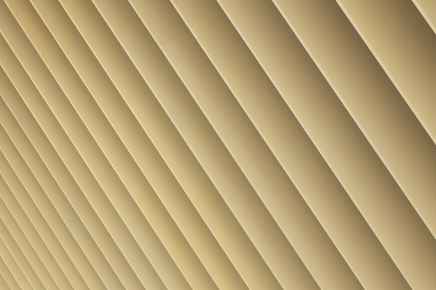 Diagonal view of beige or golden 3d stripes. louvre shutters like pattern, diagonal pattern close-up.