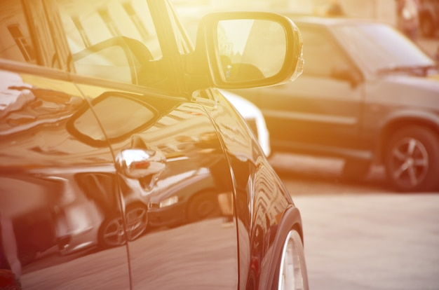 회색 타일의 사각형에 흰색 바퀴가 달린 검은 광택 자동차의 대각선보기