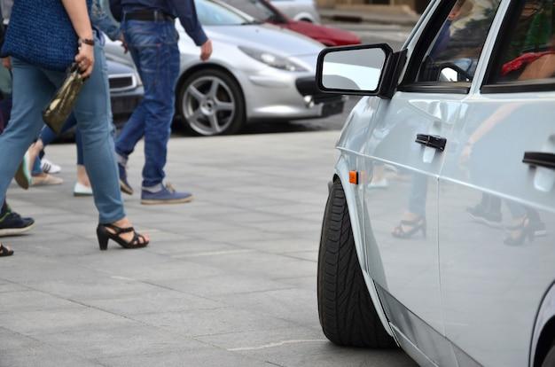 灰色のタイルの正方形の上に立っている白い光沢のある車の斜めの眺め