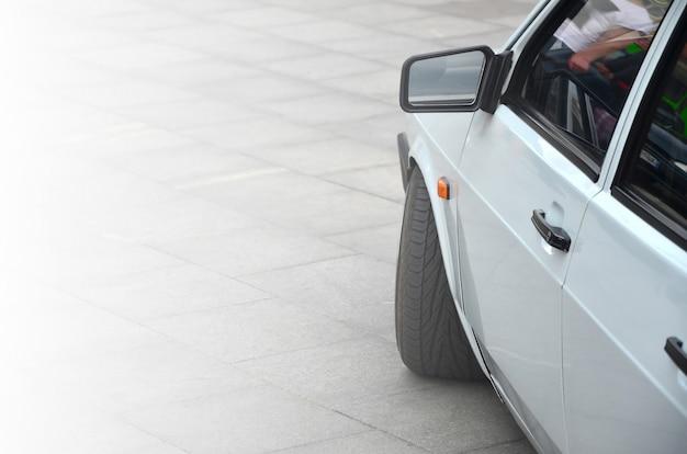 灰色のタイルの正方形の上に立つ白い光沢のある車の斜めの眺め
